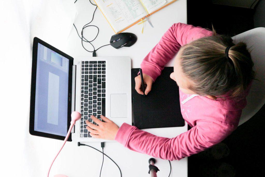 Dziewczyna w różowej bluzie siedzi przy biurku i rysuje na tablecie graficznym.