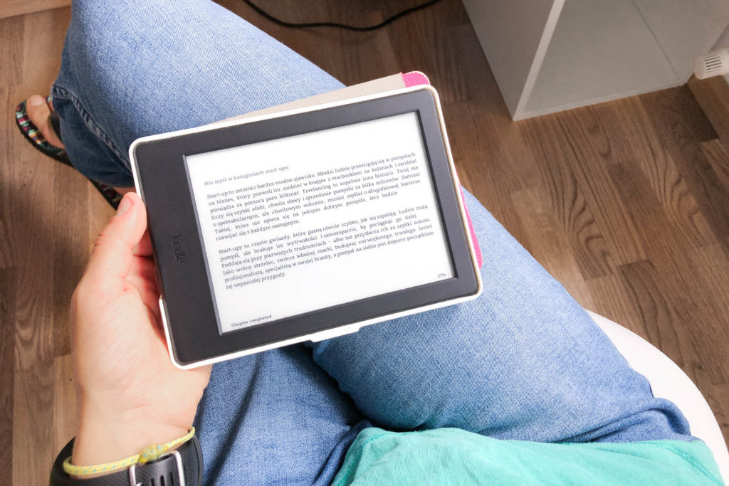 Osoba w dżinsach siedzi na krześle i czyta ebooka.